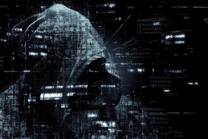 Hackers Códigos sobre un fondo oscuro con encapuchado