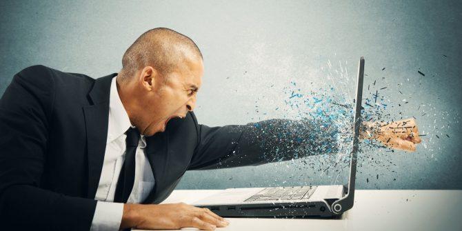 Hombre rompe pantalla de ordenador portátil con el puño