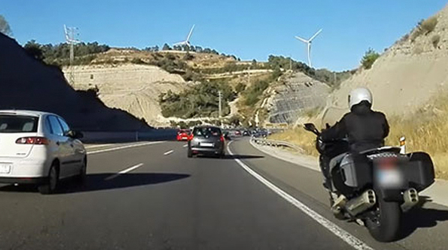 En moto por el arcén, con guantes en carretera y conectados al móvil